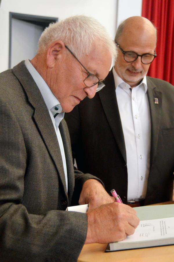 Stadtrat Jürgen Schulz unterschreibt die Urkunde zum abgelegten Diensteid. Im Hintergrund Bürgermeister Erhard Walther.